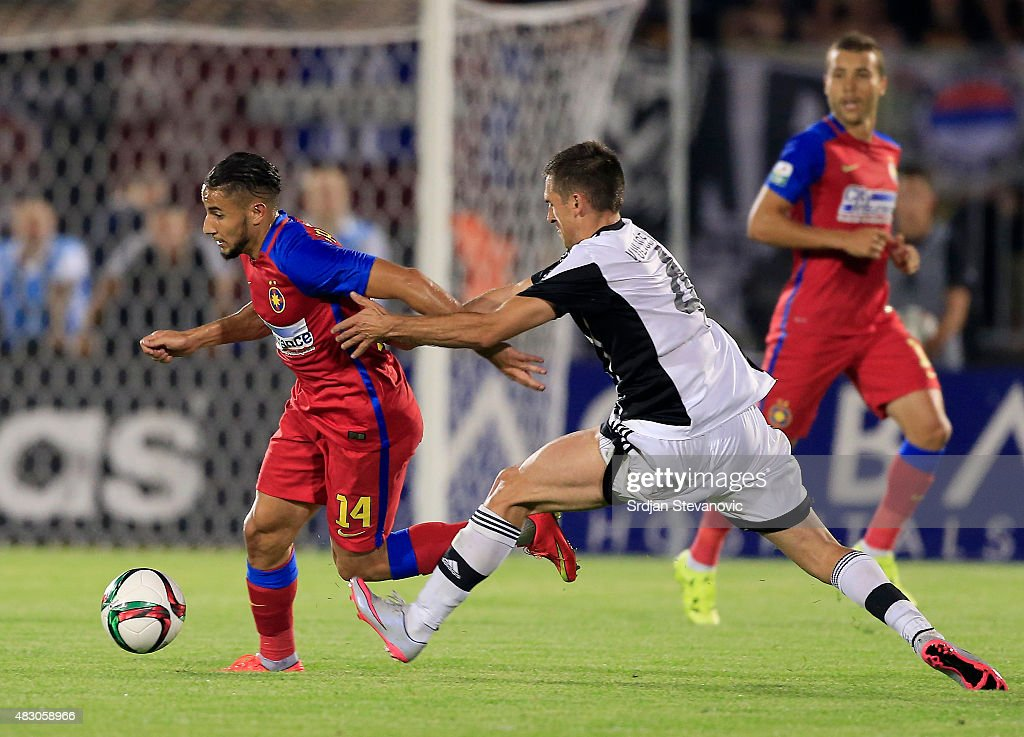 Jugurtha Hamroun (L) of FC Steaua Bucharest is challenged by Miroslav Vulicevic (R) of FC Partizan Belgrade during the UEFA Champions League Third Qualifying Round Second Leg match between FC Partizan Belgrade and FC Steaua Bucharest at FC Partizan stadium in Belgrade, Serbia on Wednesday, August 05, 2015.