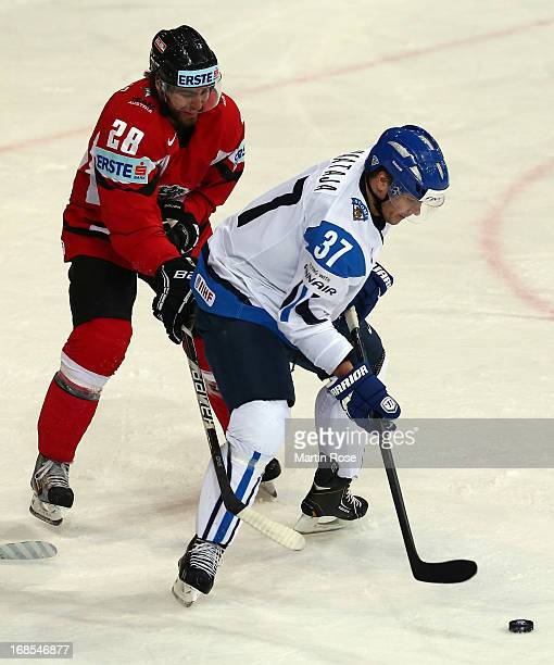 Juha Haataja of Finland and Martin Schumnig of Austria battle for the puck during the IIHF World Championship group H match between Finland and...