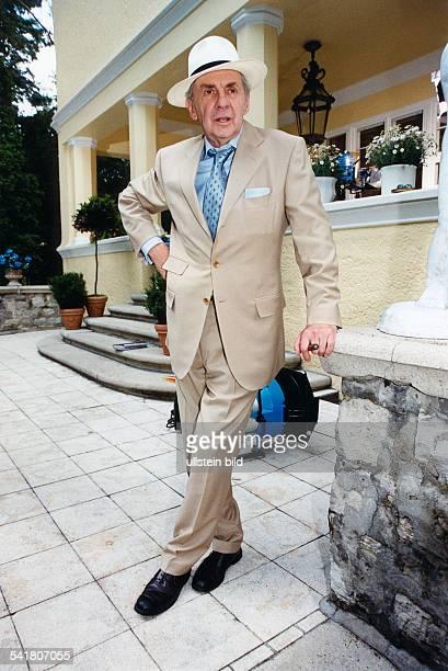 Juhnke Harald *Schauspieler Entertainer D Ganzkoerperaufnahme steht mit Hut und hellem Anzug bekleidet auf einer Terrasse 1999