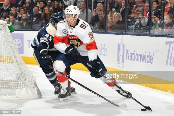 Juho Lammikko of the Florida Panthers shields the puck from the reaching stick of Lukas Sedlak of the Columbus Blue Jackets during the second period...