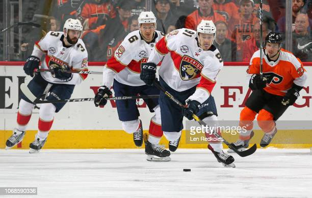 Juho Lammikko of the Florida Panthers skates the puck with Alexander Petrovic and Keith Yandle against Scott Laughton of the Philadelphia Flyers on...