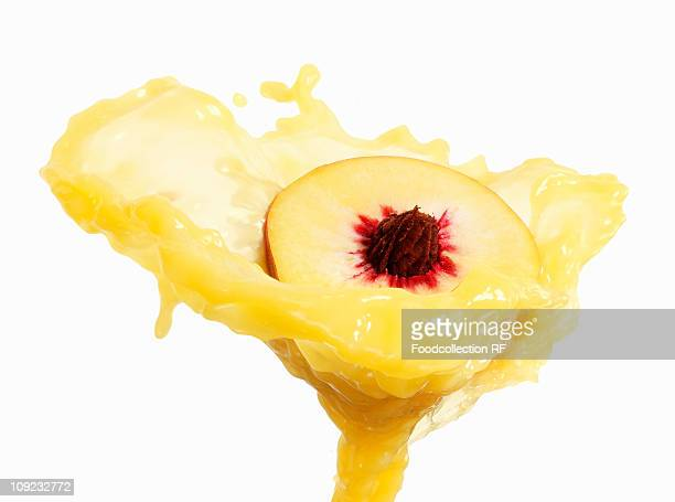 Juice splashing on peach against white background