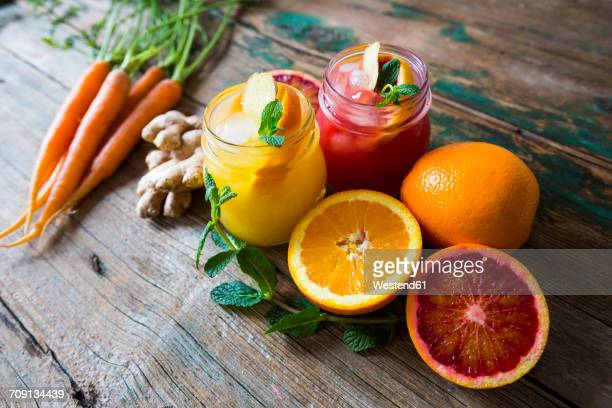 juice with oranges and ginger and mint and carrots - komplett stock-fotos und bilder