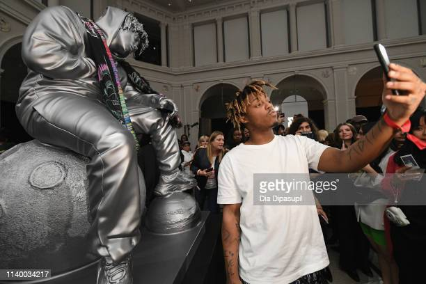 Juice WRLD poses with a sculpture of himself at Spotify's RapCaviar Pantheon at Brooklyn Museum on April 02 2019 in Brooklyn New York