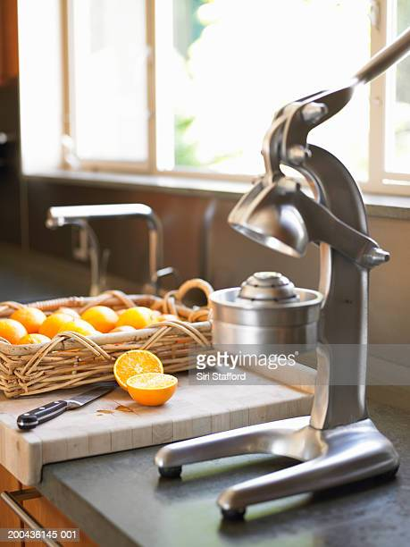 Juicer and sliced oranges on kitchen counter