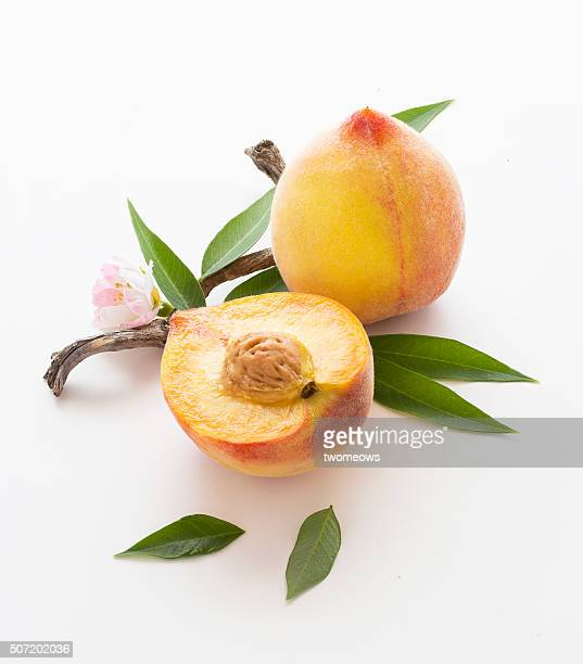 Juicy fresh cut and whole peaches with leaves on white background. Natural lighting. Stylized food image.