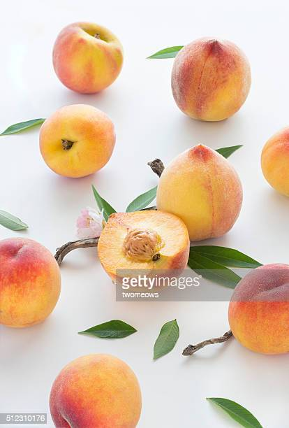 Juicy fresh cut and whole peaches with leaves on white background. Stylised food image.