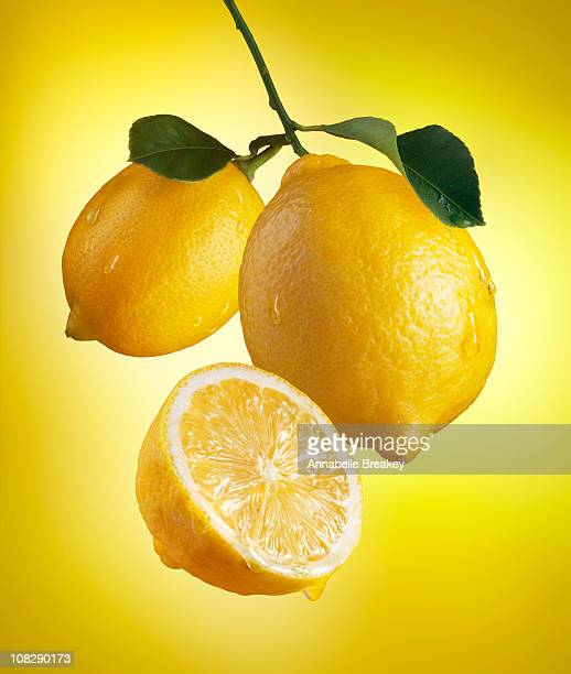 juicy lemons with drips on yellow - zitrone stock-fotos und bilder