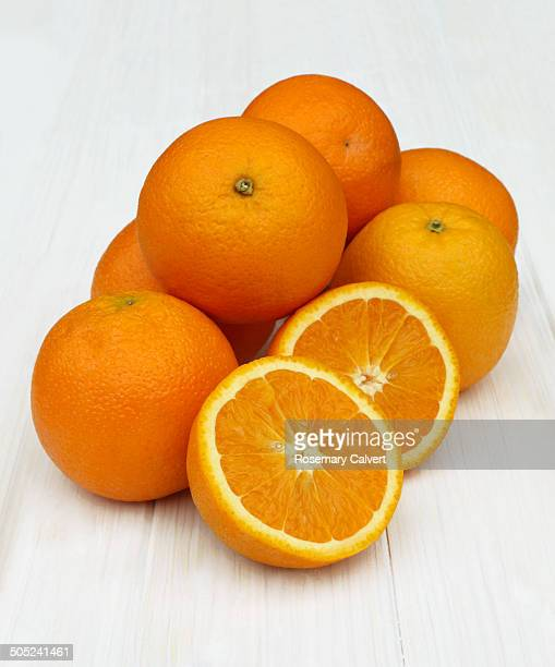 Juicy, organic oranges in a pile on white