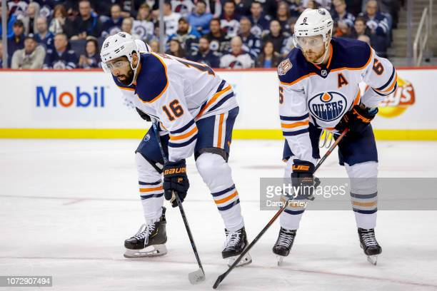 Jujhar Khaira and Adam Larsson of the Edmonton Oilers get set for a first period faceoff against the Winnipeg Jets at the Bell MTS Place on December...
