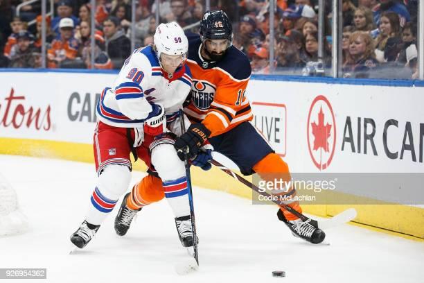Jujhar Khaira of the Edmonton Oilers battles against Vladislav Namestnikov of the New York Rangers at Rogers Place on March 3 2018 in Edmonton Canada