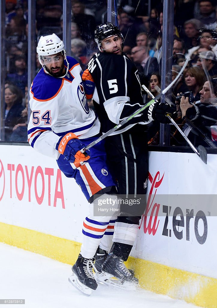 Jujhar Khaira #54 of the Edmonton Oilers checks Jamie McBain #5 of the Los Angeles Kings into the boards during the first period at Staples Center on February 25, 2016 in Los Angeles, California.