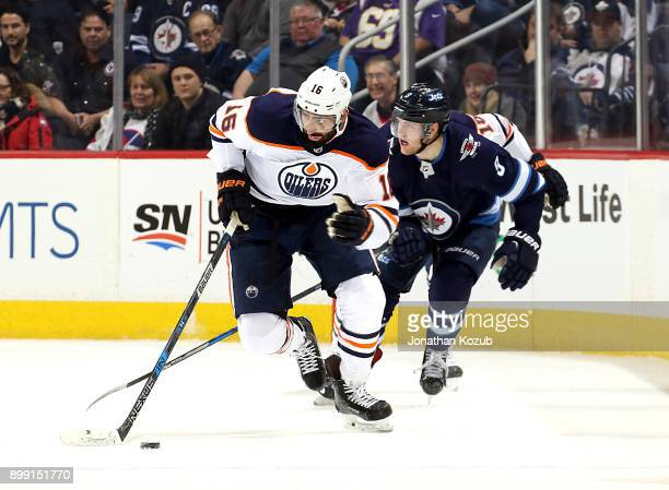 Jujhar Khaira of the Edmonton Oilers plays the puck down the ice as Andrew Copp of the Winnipeg Jets gives chase during first period action at the...