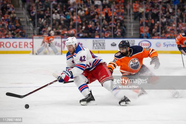 Jujhar Khaira of the Edmonton Oilers pursues Brendan Smith of the New York Rangers during the second period at Rogers Place on March 11 2019 in...