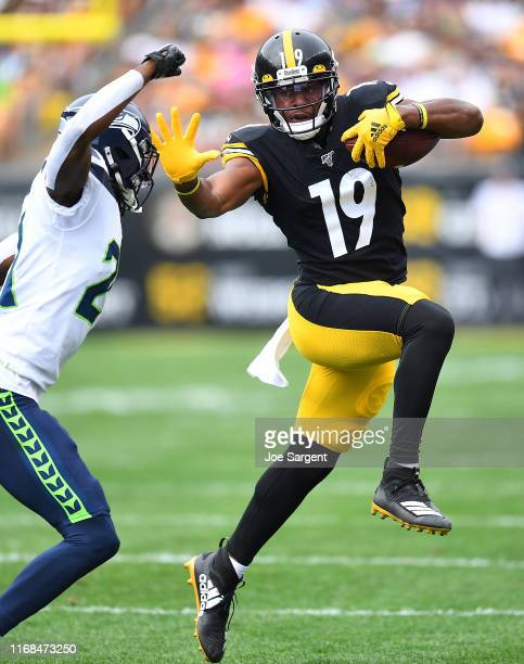 JuJu Smith-Schuster of the Pittsburgh Steelers carries the ball in front of Tre Flowers of the Seattle Seahawks during the second quarter at Heinz...