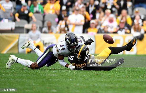 JuJu Smith-Schuster of the Pittsburgh Steelers fumbles the ball away as Marlon Humphrey of the Baltimore Ravens defends in overtime during the game...