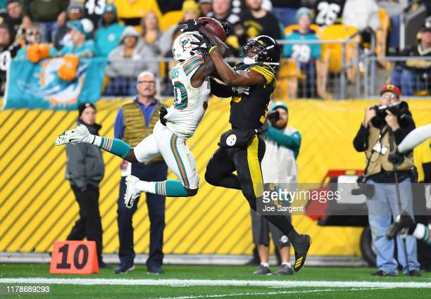 JuJu Smith-Schuster of the Pittsburgh Steelers makes a touchdown catch against Chris Lammons of the Miami Dolphins during the third quarter at Heinz...