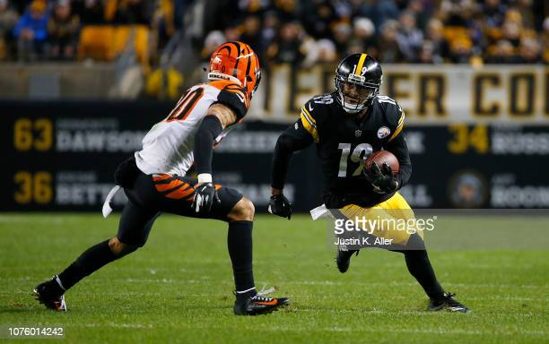 JuJu SmithSchuster of the Pittsburgh Steelers runs upfield after a catch as Jessie Bates of the Cincinnati Bengals defends in the second half during...