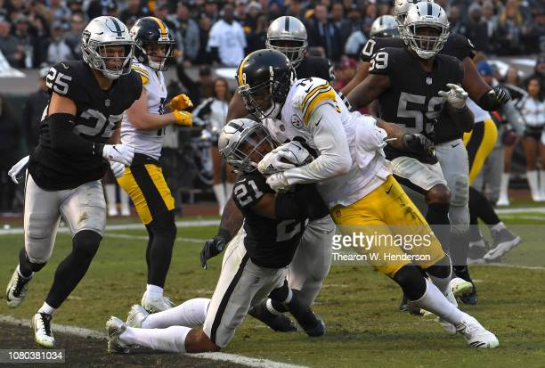 JuJu Smith-Schuster of the Pittsburgh Steelers scores a touchdown dragging Gareon Conley of the Oakland Raiders in to the endzone in the fourth...