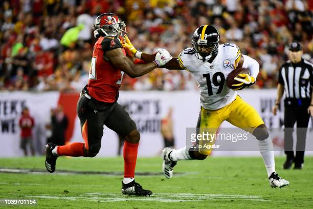 JuJu SmithSchuster of the Pittsburgh Steelers stiffarms MJ Stewart of the Tampa Bay Buccaneers on September 24 2018 at Raymond James Stadium in Tampa...
