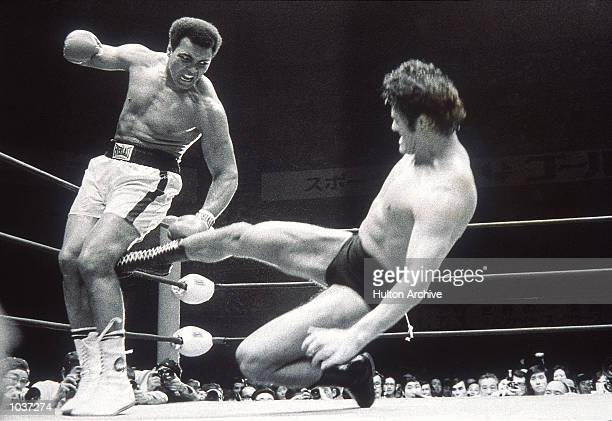 Muhammad Ali fends off a kick from wrestler Antonio Inoki during an exhibition fight in Tokyo Japan Mandatory Credit Allsport Hulton/Archive