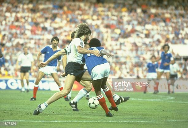 Manni Kaltz of West Germany tackles Jean Tigana of France for the ball during the World Cup Semi Finals match in Barcelona Spain West Germany won 54...