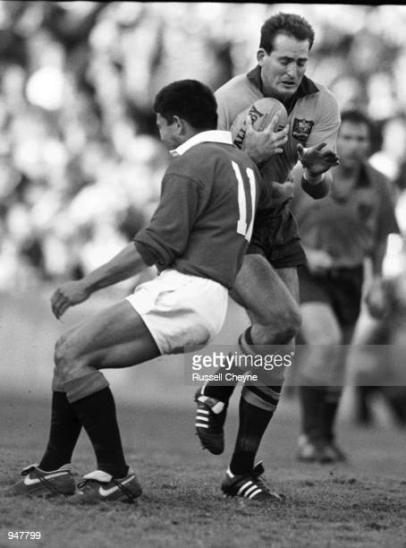 David Campese of Australia is tackled by Rory Underwood of the British Lions during the British Lions tour to Australia match played in Sydney...