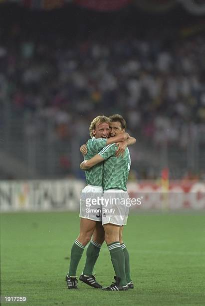 Andreas Brehme and Klaus Augenthaler of West Germany embrace after their victory in the World Cup semifinal against England at the Delle Alpi Stadium...