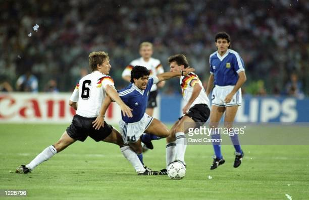 Diego Maradona of Argentina is brought down by Guido Buchwald and Lothar Mattheus of West Germany during the World Cup final at the Olympic Stadium...
