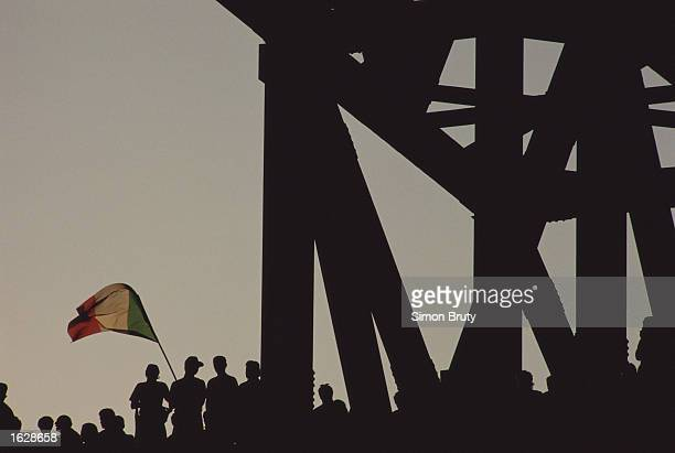 Silhouette of Italian supporters with their national flag during the World Cup semifinal against Argentina at the San Paolo Stadium in Naples Italy...