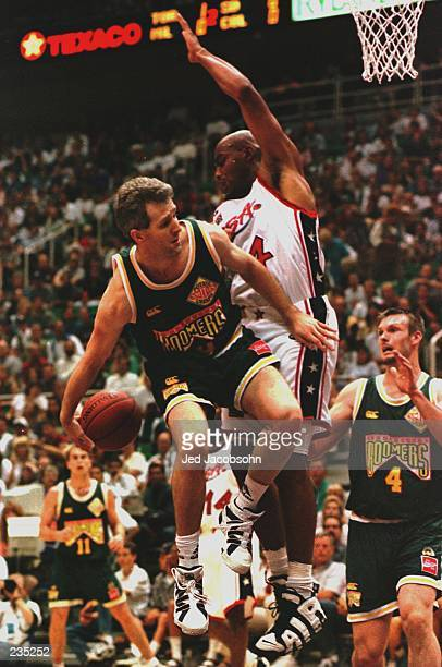Andrew Gaze of Australia passes behind his back to teammate Tony Ronaldson as Olympic 'Dream Team' member Charles Barkley of the USA defends during a...