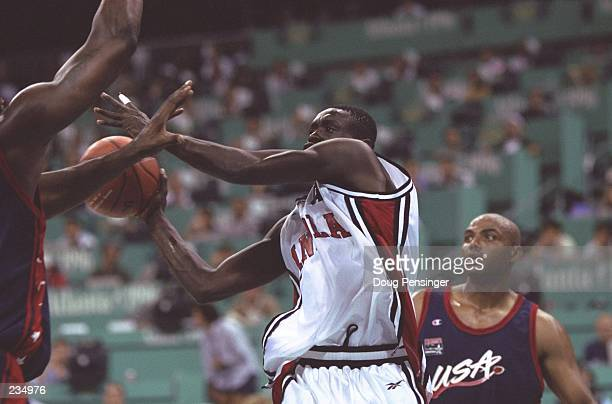 Edmar Victoriano, center, of Angola tries to shoot past the arms of an unidentified Dream Team player as Charles Barkley watches during the USA v...