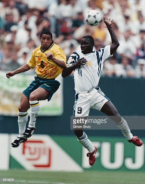 Forward George Weah of the FIFA World Stars and defenseman Roberto Carlos of the Brazil All Stars go up for the ball in the second half of their game...
