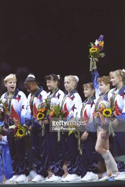 Injured Kerri Strug bandaged leg joins the gymnastics team from the USA with their gold medal for the team gymnastics event at the Georgia Dome at...