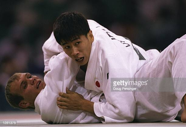 Ivan Netov, below, is pinned by Yukimasa Nakamura of Japan during their men's 65kg lightweight match at the Georgia World Congress Center at the 1996...