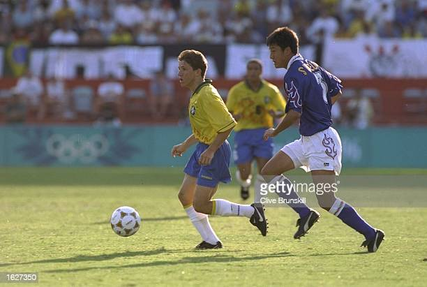 Juninho of Brazil and Hideto Suzuki of Japan compete for the ball during the match against Japan at the Centennial Olympic Games in Atlanta at the...