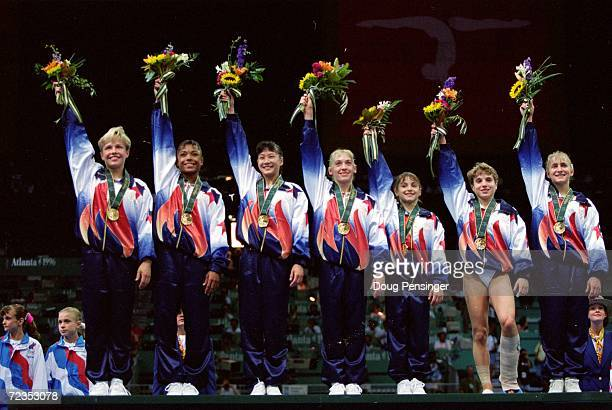 Kerri Strug of the USA waves to the crowd from the winners podium after injuring her ankle during her routine at the Georgia Dome in the 1996 Olympic...