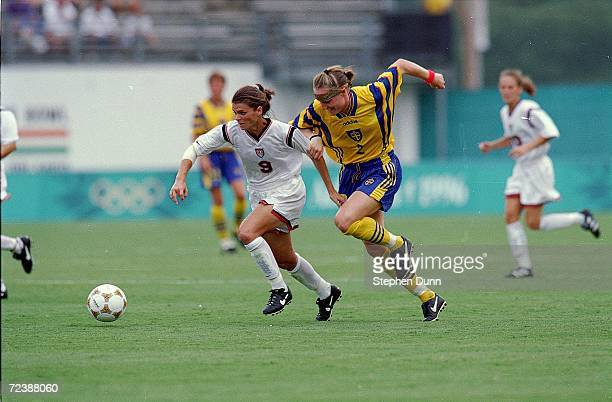 Mia Hamm of Team USA runs for the ball with Cecilia Sandell of Team Sweden during the 1996 Olympic Games at the Citrus Bowl in Orlando, Florida. Team...
