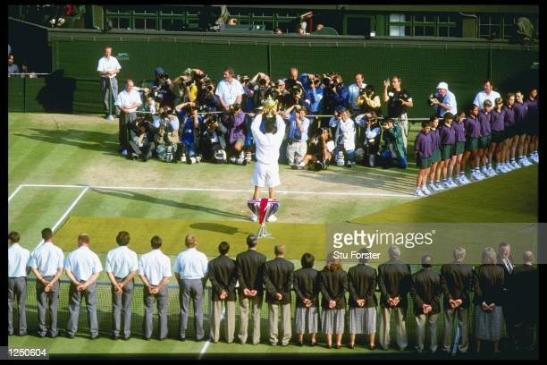 Richard Krajicek of the Netherlands lifts the mens singles trophy in front of the press gallery after defeating Malivai Washington of the USA in...