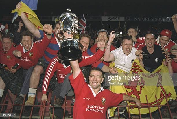 John Bentley of the British Lions holds aloft the trophy in front of Lions supporters after the third test match against South Africa at Ellis Park...