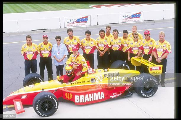 Scott Pruett of the United States poses with his team and car at the United States 500 at the Michigan Speedway in Brooklyn Michigan
