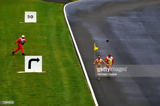 A streaker runs on the track before the British Grand Prix at the Silverstone circuit in Northampton England Mandatory Credit Michael Cooper/Allsport