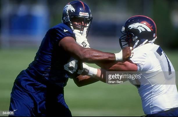 Defensive lineman Duane Ashman and offensive tackle Trey Teague of the Denver Broncos in action during the 1998 Denver Broncos training camp at the...