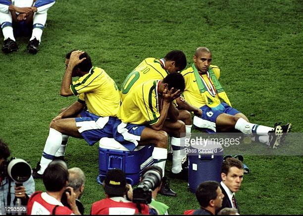 Edmundo Rivaldo Cafu and Roberto Carlos of Brazil hang their heads in despair after losing the World Cup Final against France at the Stade de France...