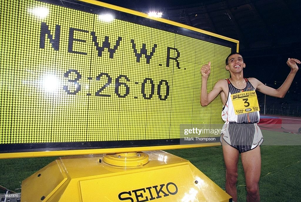 Hicham El Guerrouj of Morocco stands next to the clock showing his New World Record time of 3:26.00 minutes for the 1500 metres event during the IAAF Golden League Golden Gala at the Olympic Stadium in Rome. \ Mandatory Credit: Mark Thompson/Allsport