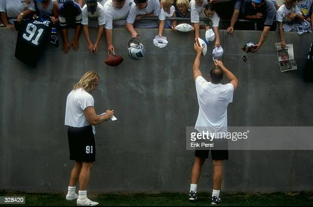 Linebacker Kevin Greene and quarterback Kerry Collins of the Carolina Panthers sign autographs during the 1998 Carolina Panthers Training Camp at the...