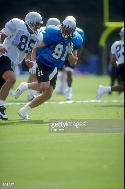 Linebacker Kevin Greene of the Carolina Panthers in action against teammate tight end Wesley Walls during the 1998 Carolina Panthers Training Camp at...