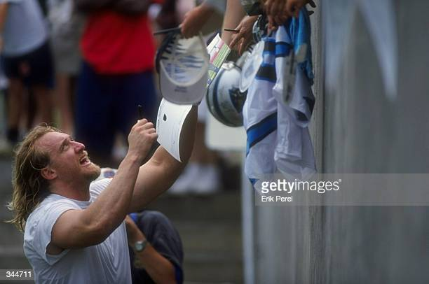 Linebacker Kevin Greene of the Carolina Panthers signs autographs during the Carolina Panthers training camp at Wofford College in Spartanburg, South...
