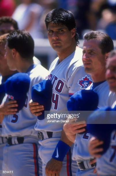 Outfielder Jose Canseco of the Toronto Blue Jays looks on during the singing of the National Anthem before the game against the Chicago White Sox at...