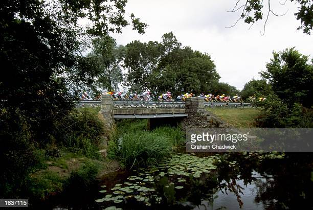 The peleton rides across a bridge during Stage 5 of the 1998 Tour De France from CholetChateauroux France Mandatory Credit Graham Chadwick /Allsport